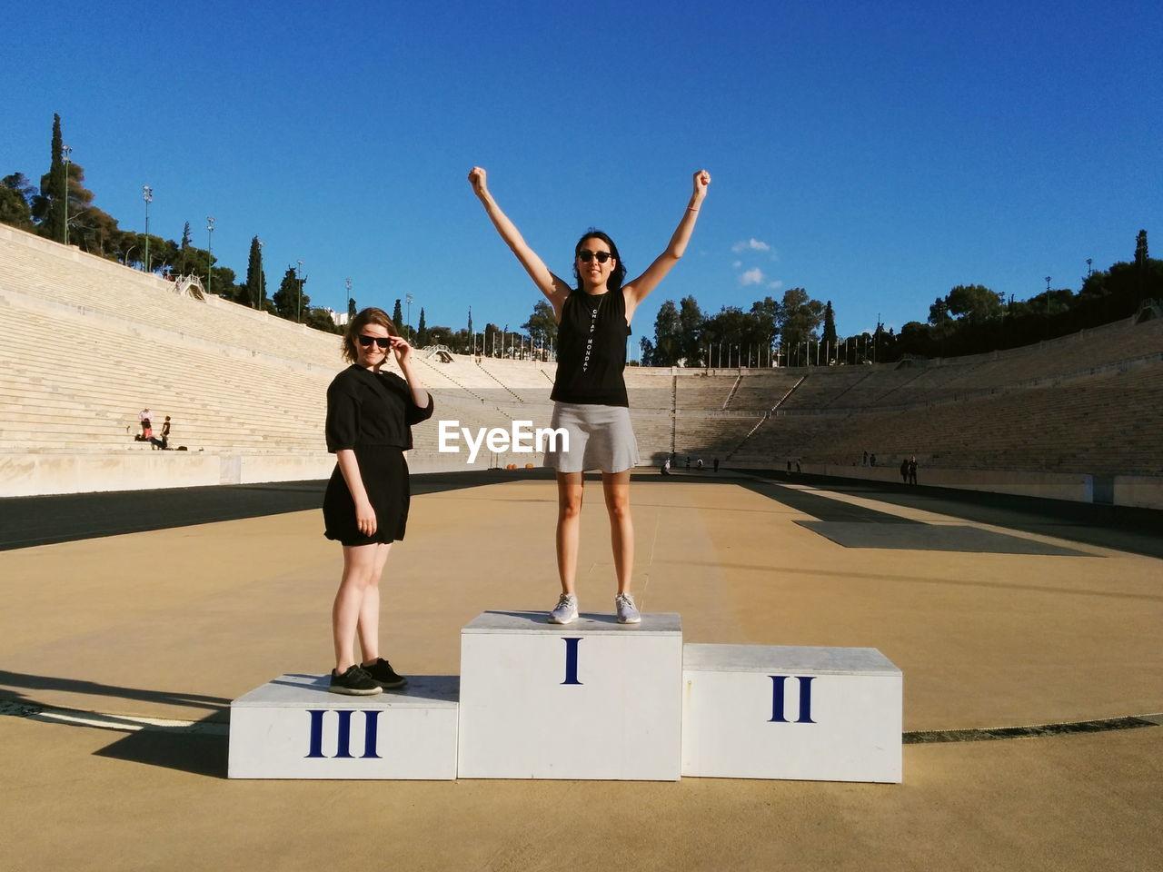 Portrait Of Smiling Friends On Winners Podium At Panathinaiko Stadium