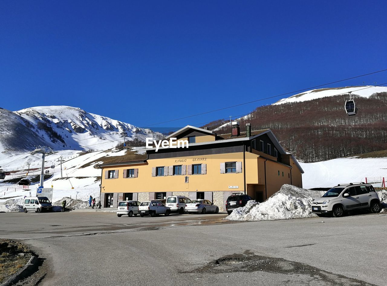 cold temperature, winter, sky, snow, building exterior, transportation, architecture, mountain, clear sky, built structure, mode of transportation, blue, day, nature, building, copy space, motor vehicle, car, land vehicle, no people, outdoors, snowcapped mountain