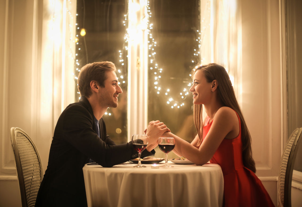 Couple holding hands while sitting at table in restaurant