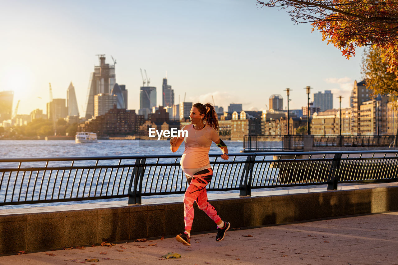 Pregnant woman running on promenade in city during sunset