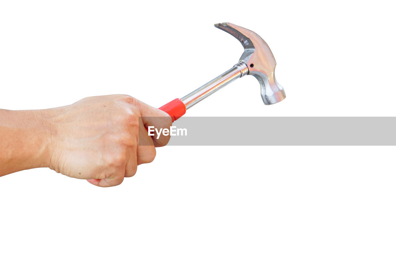 Close-up of hand holding hammer against white background