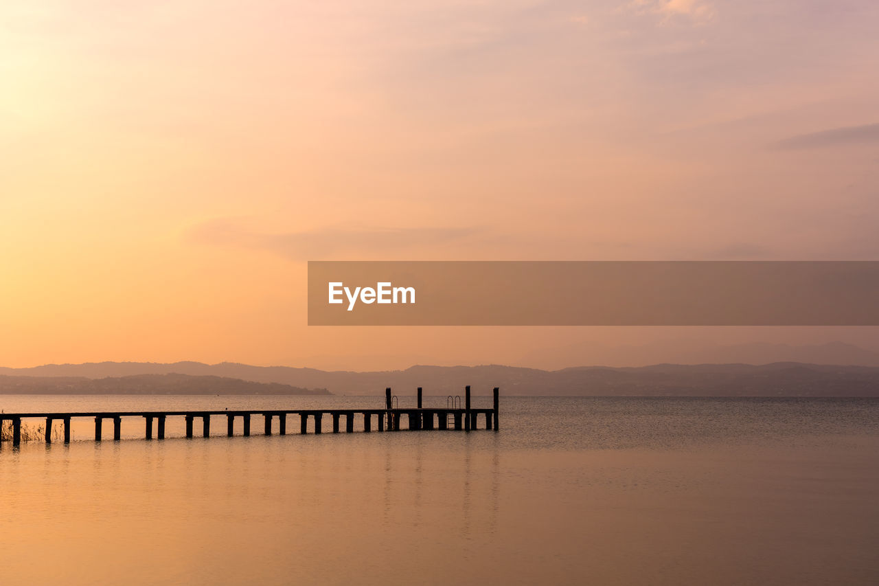 sunset, sky, water, scenics - nature, beauty in nature, tranquil scene, tranquility, sea, orange color, cloud - sky, waterfront, idyllic, pier, nature, silhouette, non-urban scene, no people, built structure, reflection, outdoors, post, wooden post