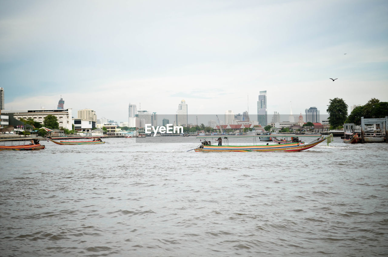 Boats on river against sky