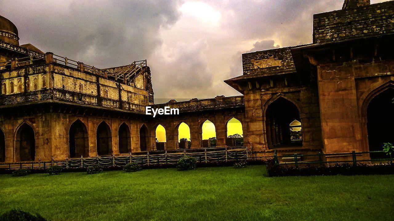 arch, architecture, built structure, sky, history, ancient, cloud - sky, grass, building exterior, no people, outdoors, day, travel destinations, ancient civilization, nature