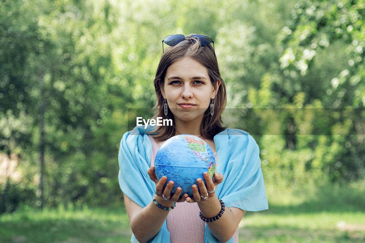 Portrait of woman holding globe