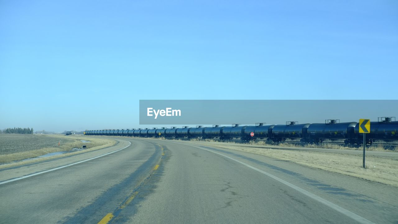 Empty Road By Freight Train Against Clear Sky