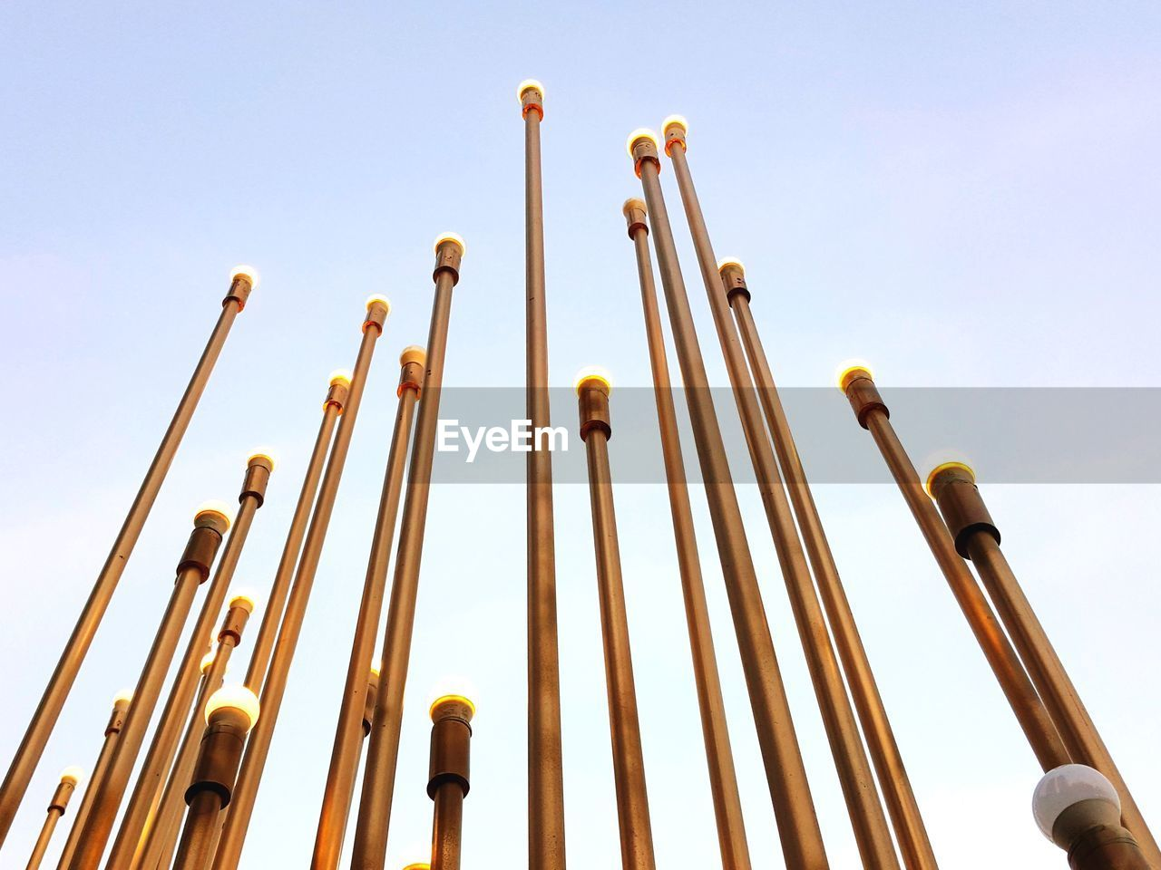 no people, sky, metal, low angle view, still life, yellow, large group of objects, clear sky, nature, day, close-up, focus on foreground, wood - material, side by side, gold colored, rod, blue, sunlight, outdoors, studio shot