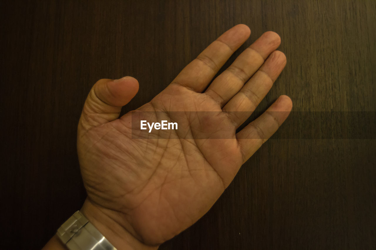 Cropped hand of man gesturing on wooden table