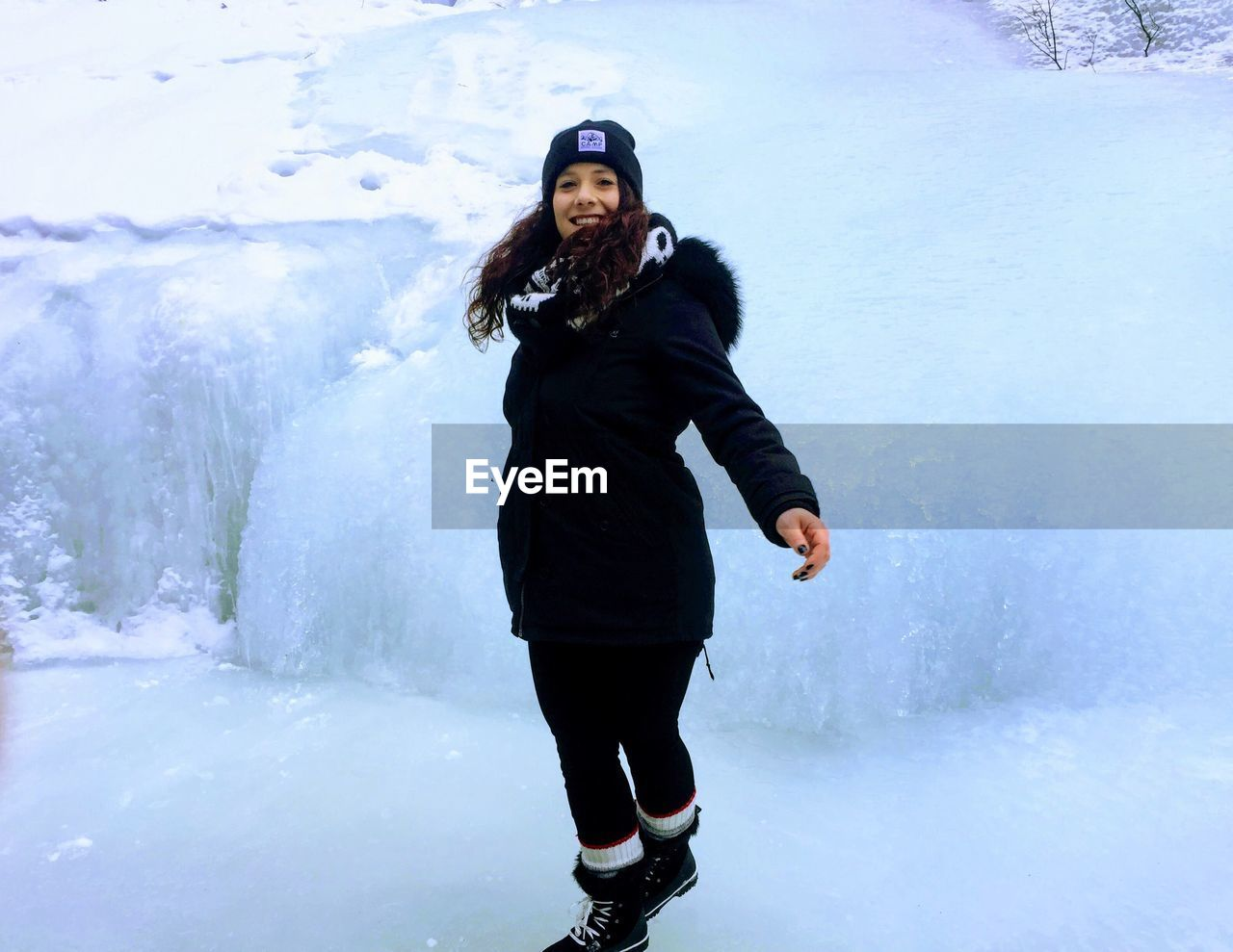 FULL LENGTH PORTRAIT OF HAPPY WOMAN STANDING ON SNOW