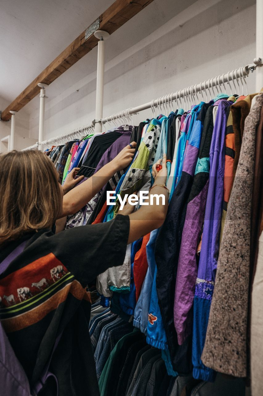 variation, choice, hanging, rack, indoors, retail, coathanger, real people, clothing, lifestyles, women, people, clothes rack, collection, leisure activity, casual clothing, large group of objects, rear view, in a row