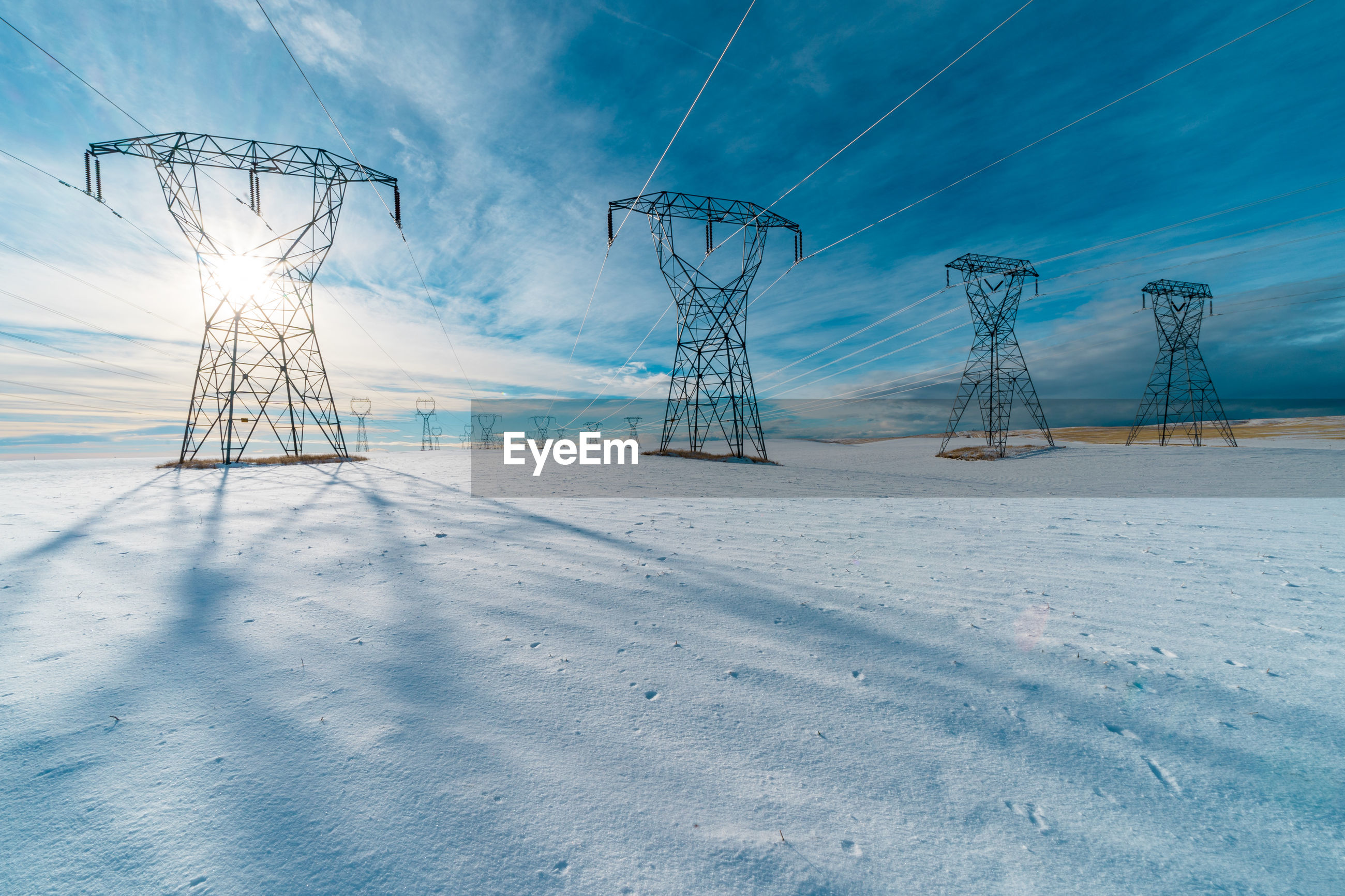 Electricity pylons on snow covered landscape
