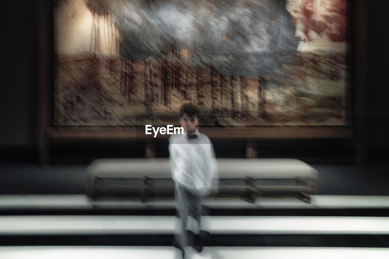 BLURRED MOTION OF MAN WALKING IN WINDOW