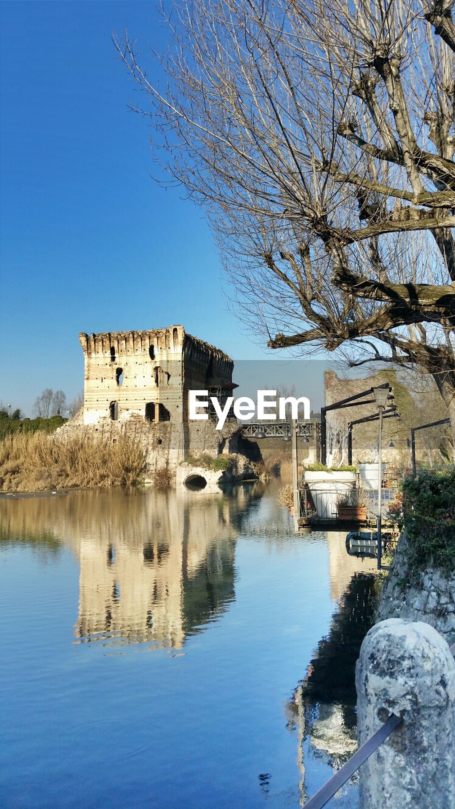 water, architecture, building exterior, built structure, tree, clear sky, nautical vessel, waterfront, transportation, river, reflection, mode of transport, day, nature, lake, outdoors, boat, house, old, bare tree