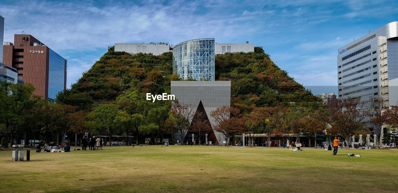 built structure, architecture, building exterior, plant, grass, tree, sky, day, office building exterior, nature, building, city, park, incidental people, cloud - sky, group of people, skyscraper, park - man made space, tower, real people, modern, outdoors