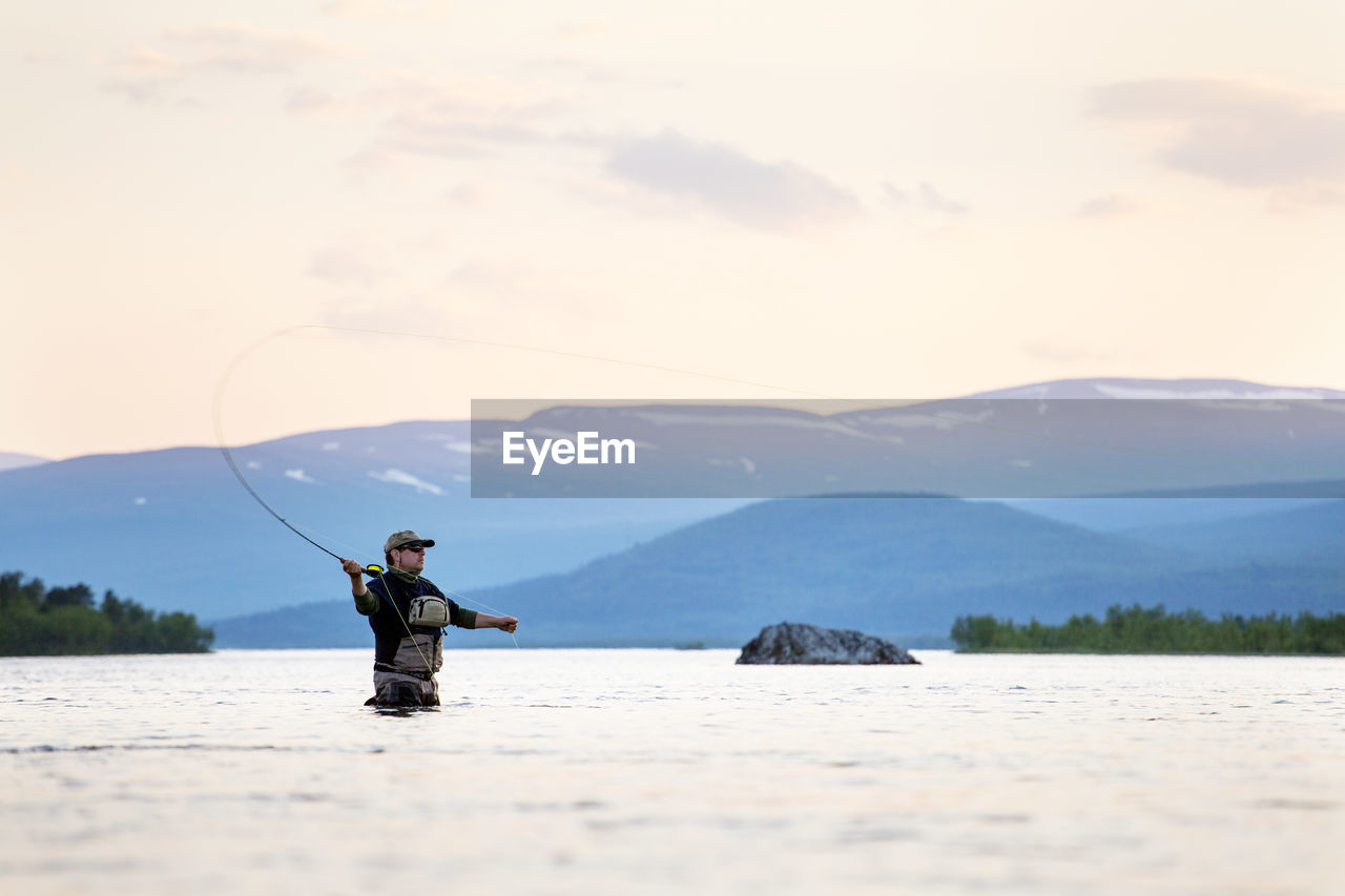 MAN ON LAKE AGAINST MOUNTAINS