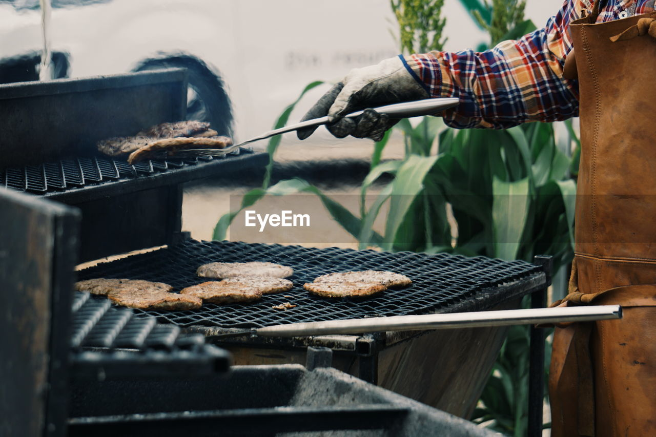 Midsection Man Preparing Food On Barbecue Grill