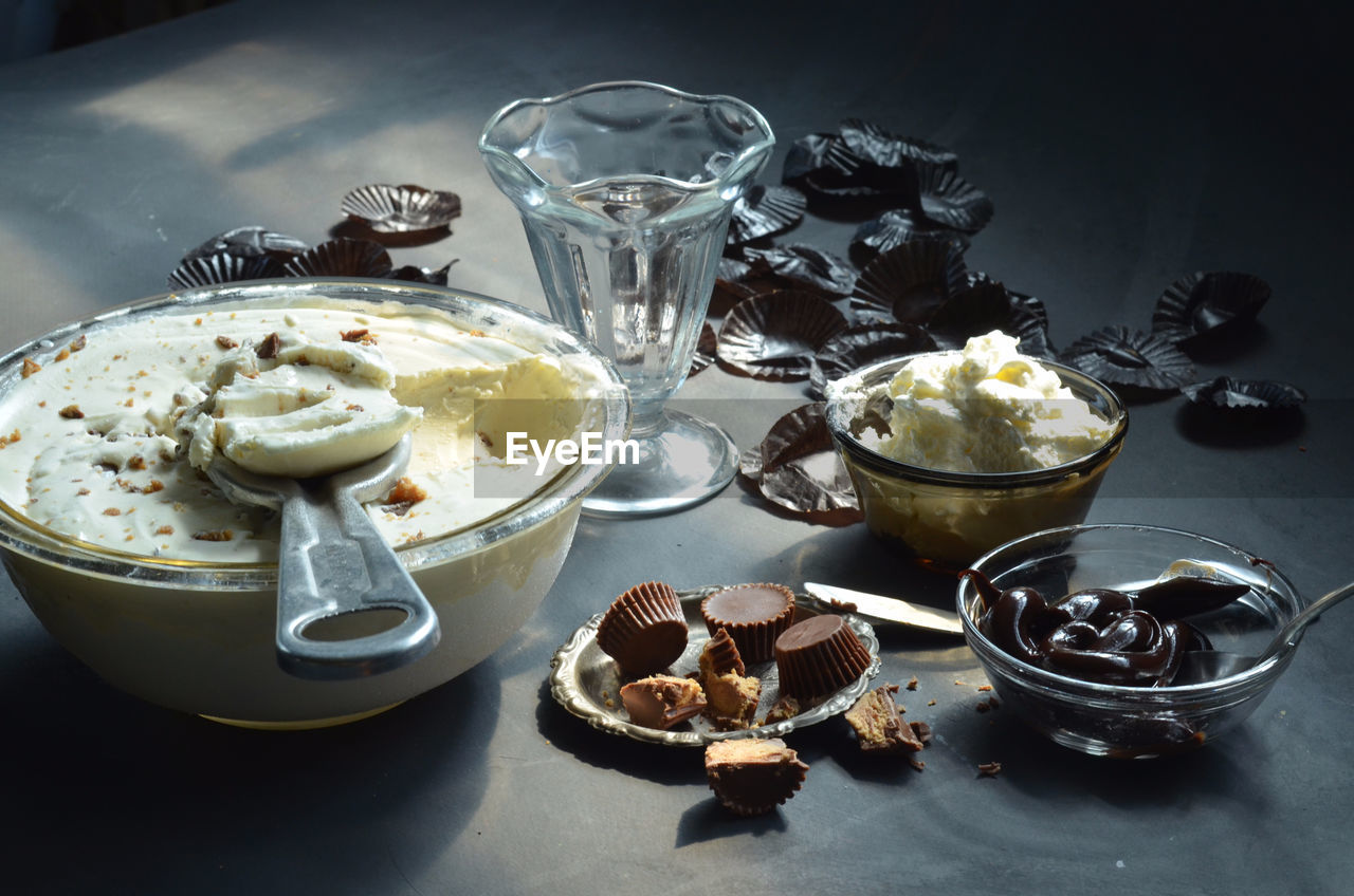 High angle view of ice cream in bowls with peanut butter cupcakes and chocolates on table