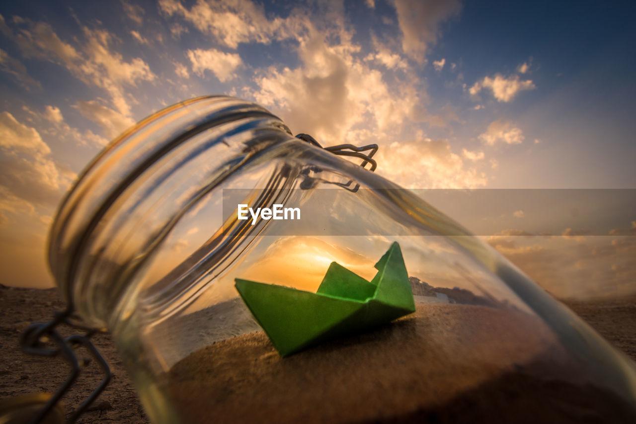 CLOSE-UP OF ORANGE PAPER ON BEACH