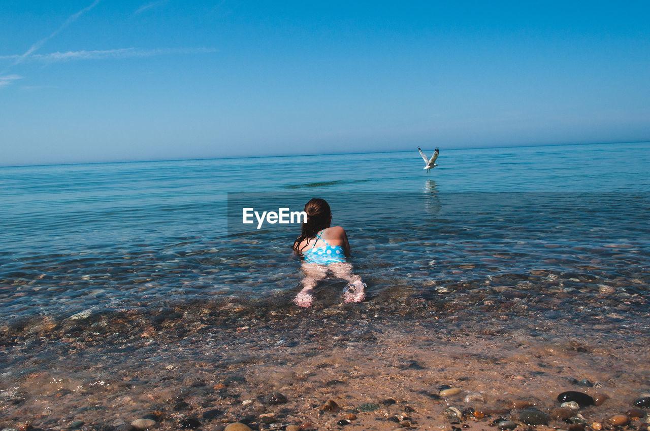 Rear View Of Girl Lying In Sea