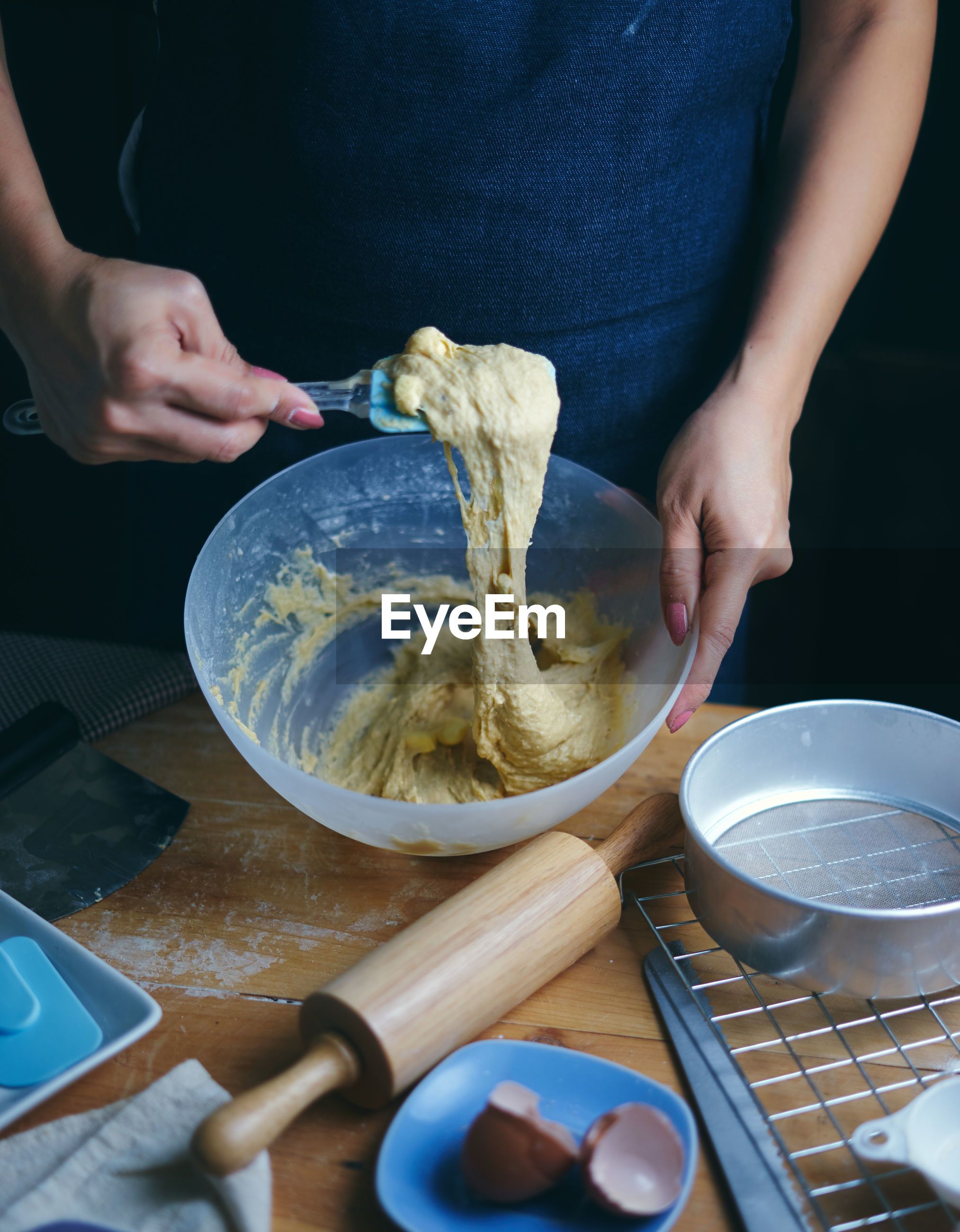 Close-up of woman preparing batter in bowl at table