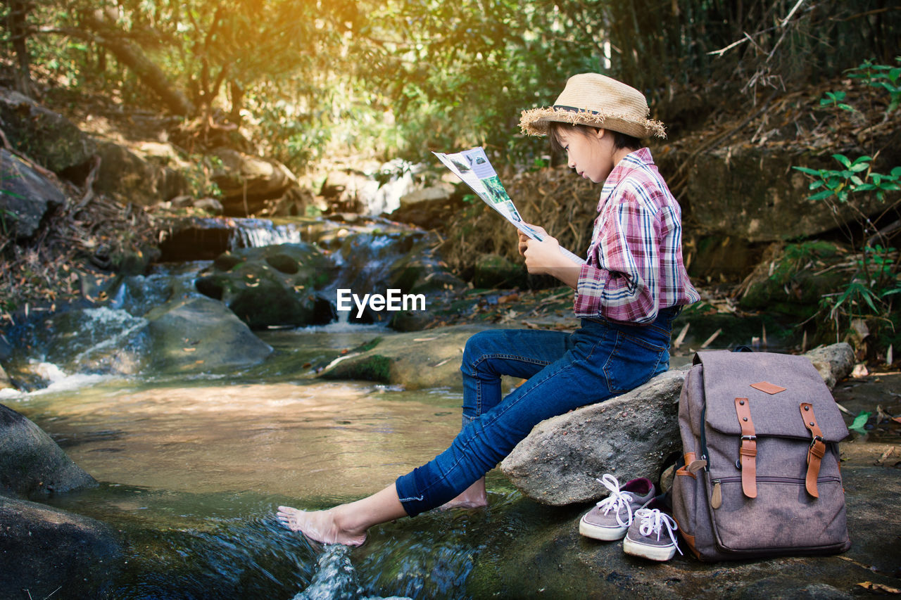 Girl reading paper while sitting on rock at river