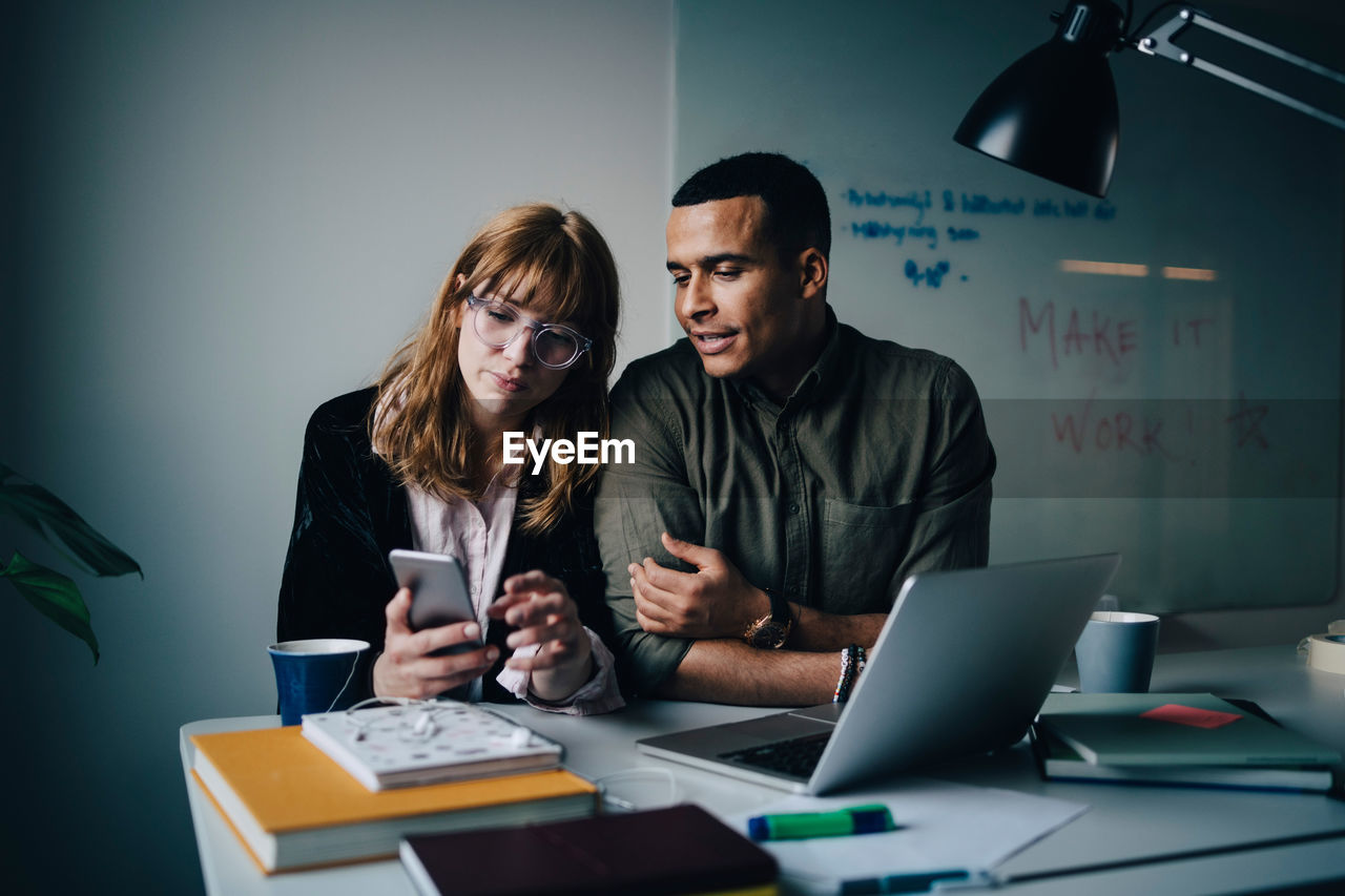 technology, wireless technology, two people, communication, computer, laptop, adult, business, table, using laptop, real people, connection, office, women, young adult, indoors, working, young women, men, teamwork, coworker
