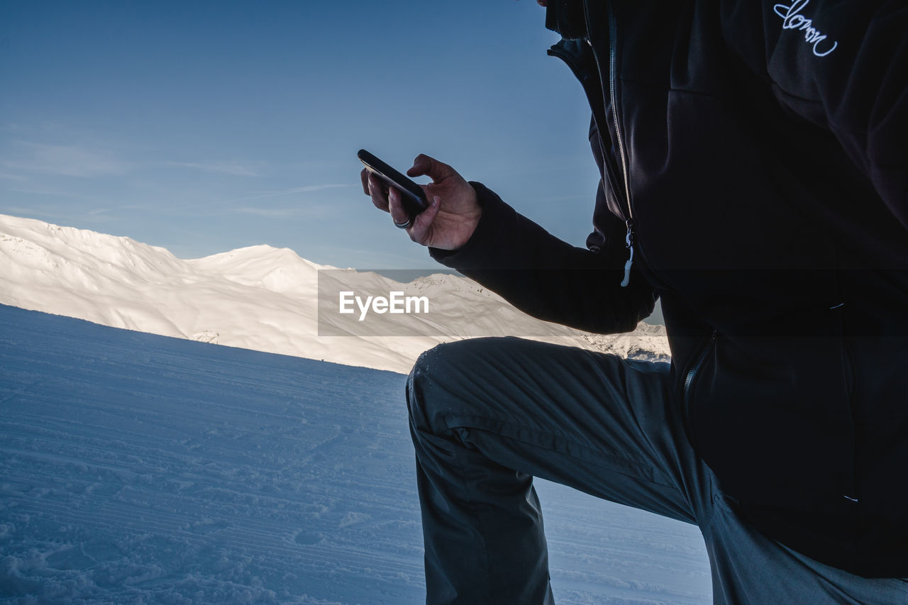 Midsection of man using mobile phone on snow covered mountain against sky