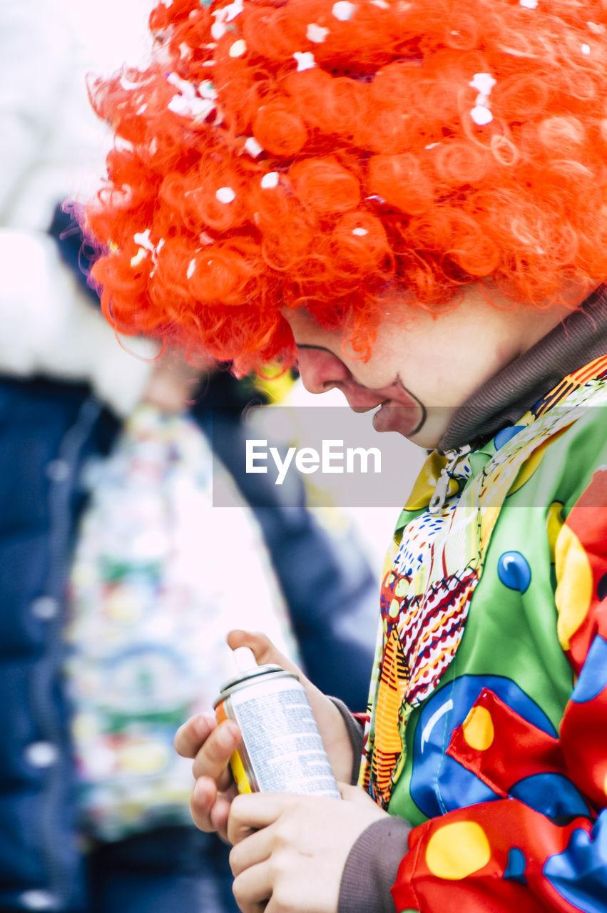 Side view of teenage boy wearing clown costume