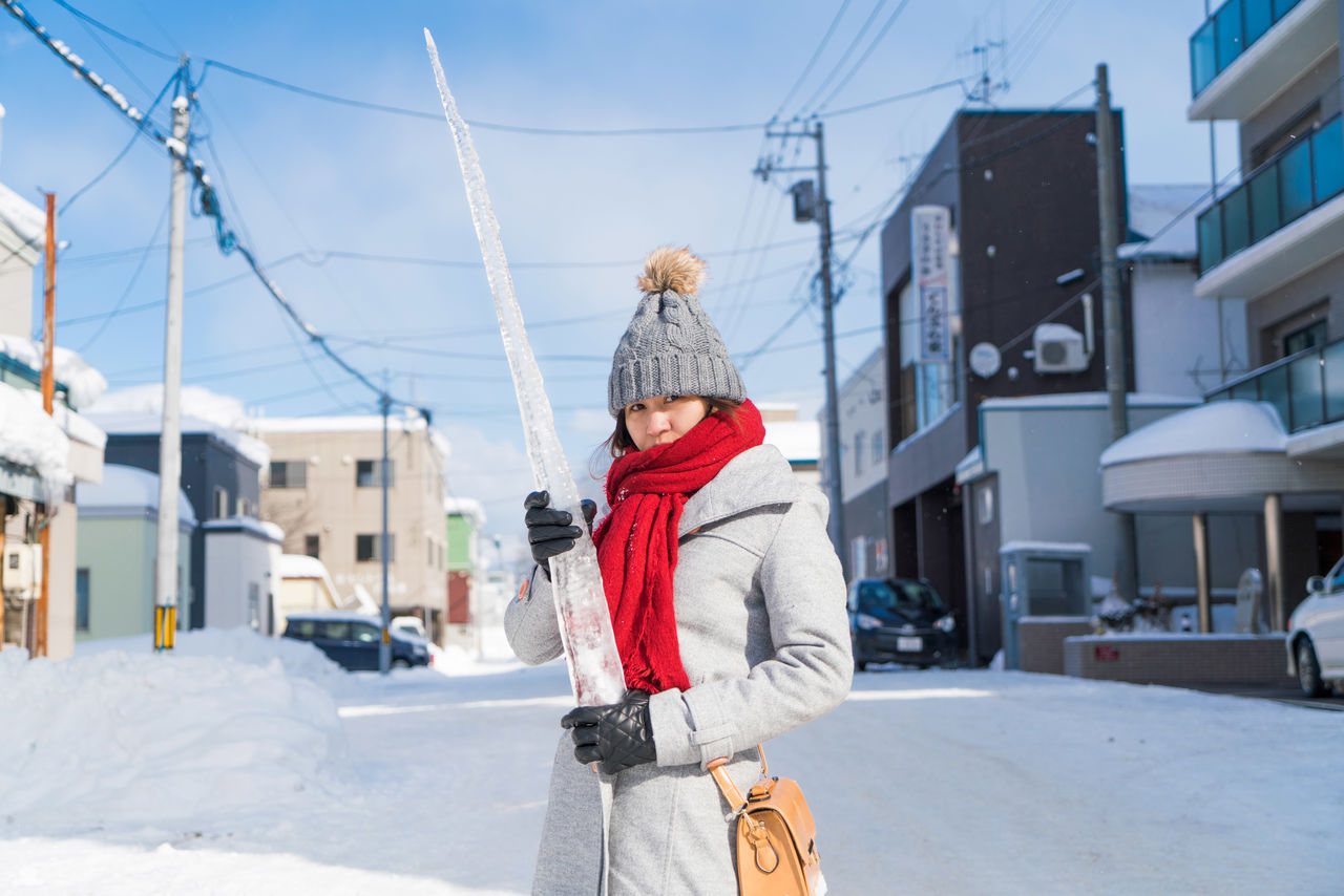 Portrait Of Woman Holding Icicle While Standing On Snow