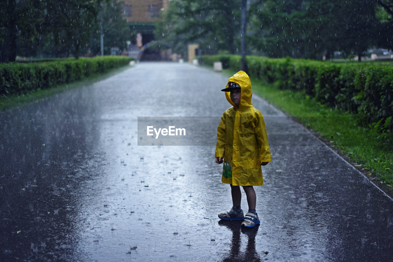 Full Length Of Boy In Yellow Raincoat