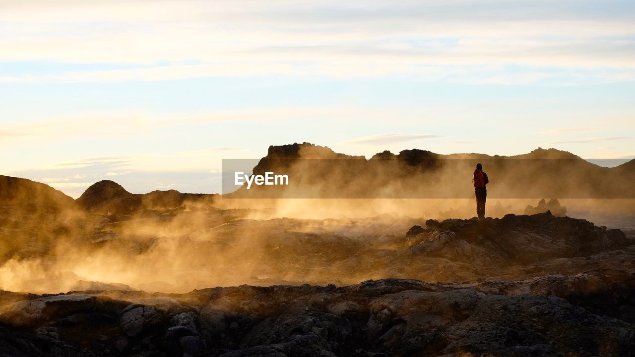 Man On Rock Formations Against Sky