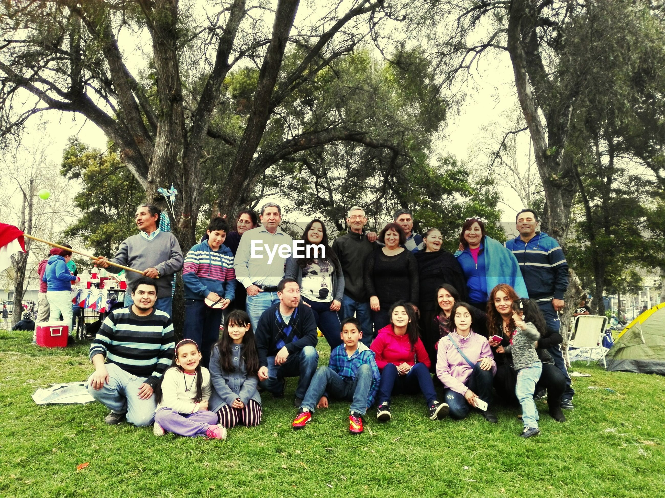 grass, lifestyles, leisure activity, togetherness, large group of people, men, person, tree, park - man made space, casual clothing, field, bonding, green color, full length, enjoyment, friendship, girls, park, sitting