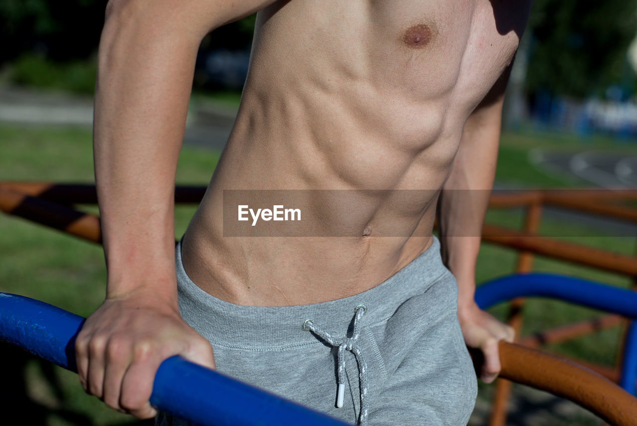 exercising, healthy lifestyle, muscular build, lifestyles, strength, one person, shirtless, real people, focus on foreground, sport, men, midsection, sports training, wellbeing, sports clothing, human body part, vitality, leisure activity, day, abdominal muscle, body conscious, shorts, masculinity