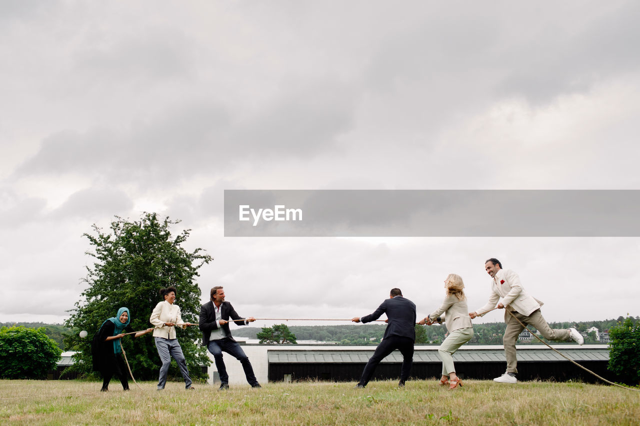 PEOPLE STANDING ON BENCH AGAINST CLOUDY SKY