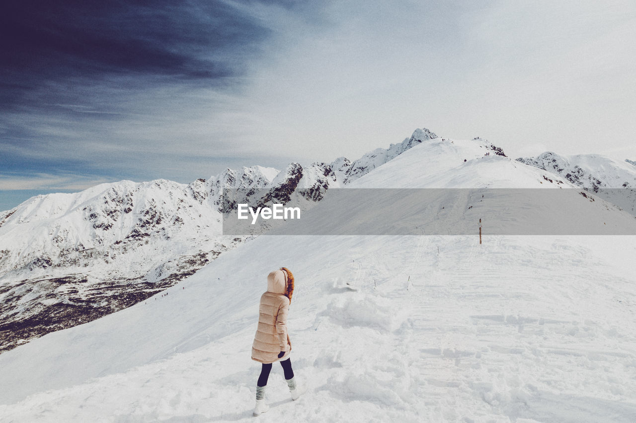 Woman Walking On Snow Covered Landscape