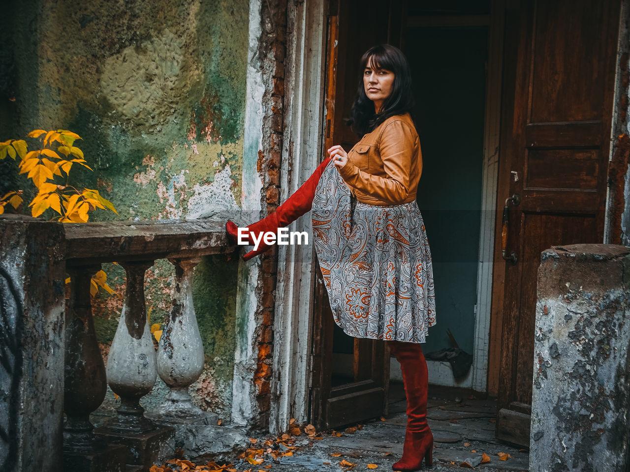 Full length portrait of woman standing outside abandoned house