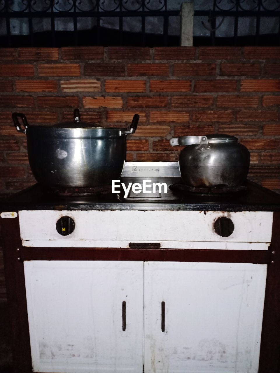 household equipment, kitchen, domestic kitchen, kitchen utensil, domestic room, home, appliance, stove, indoors, no people, metal, still life, wall - building feature, container, wood - material, cooking utensil, brick wall, cooking pan, burner - stove top, pan, steel, saucepan