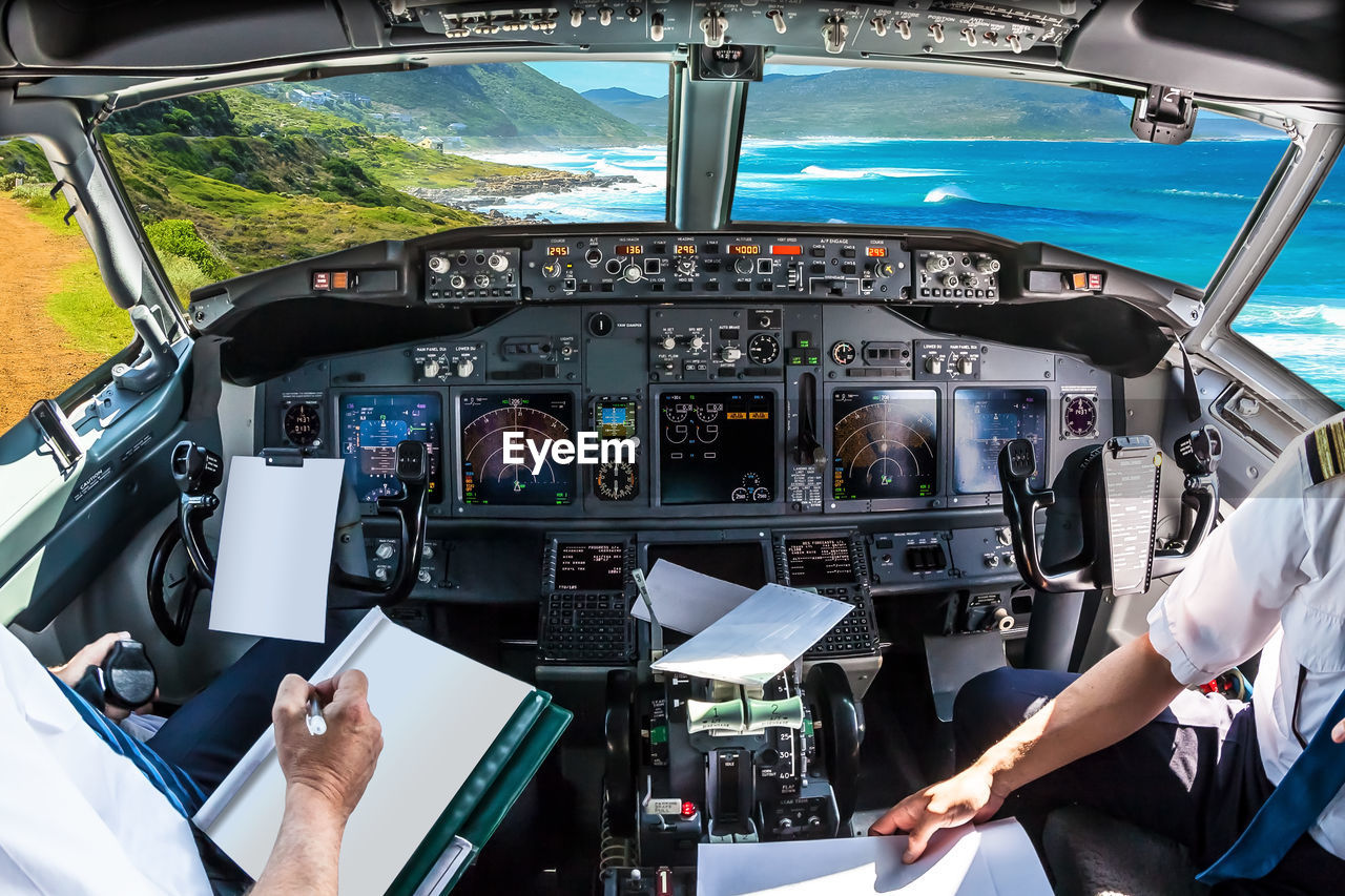 Fish-eye lens shot of pilots working in airplane by cockpit