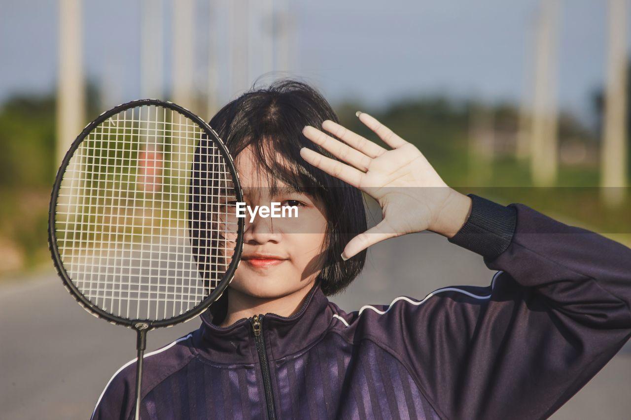 Portrait of teenager sport girl playing with badminton racket.