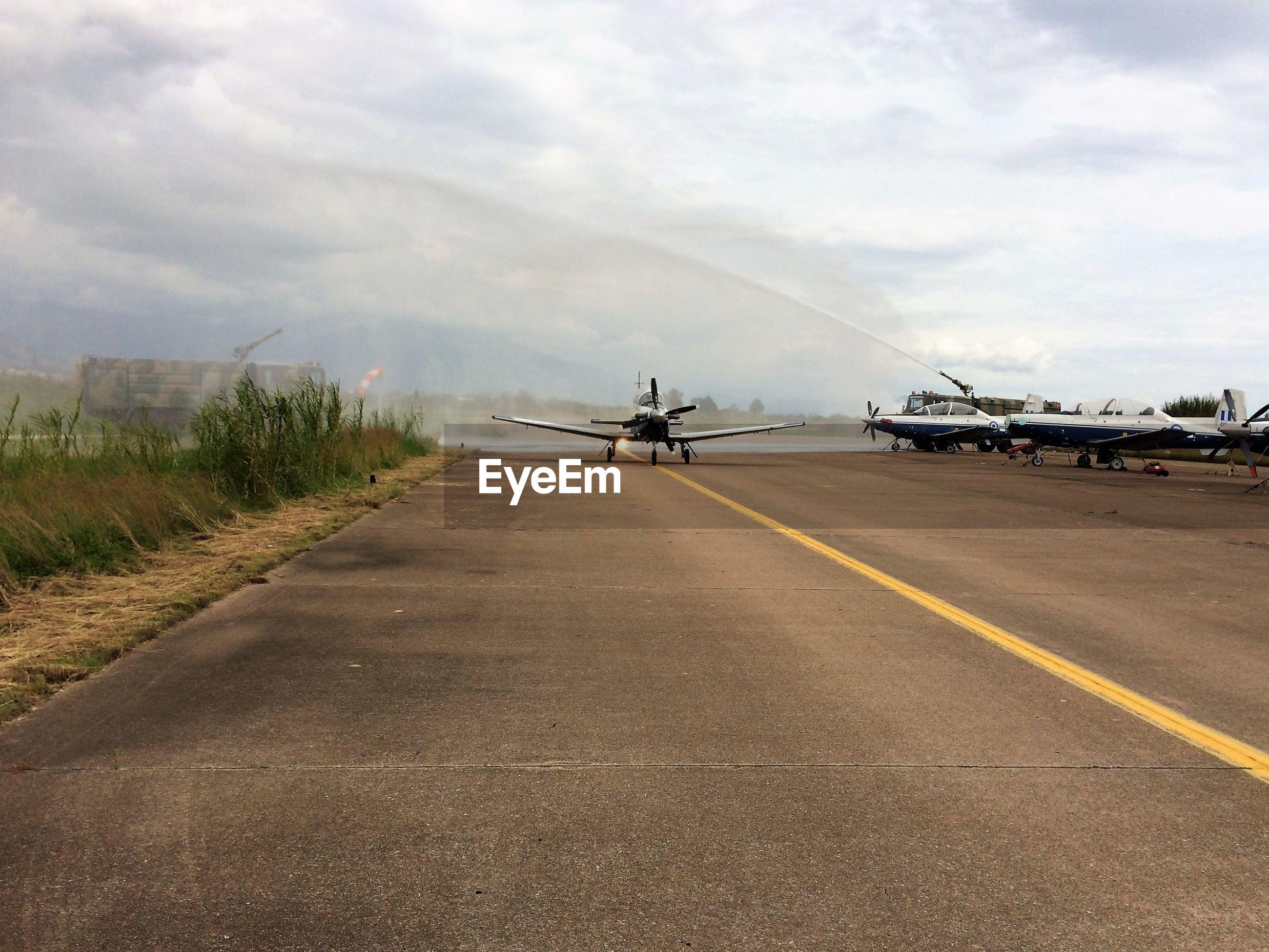 Airplanes at airport runway against sky