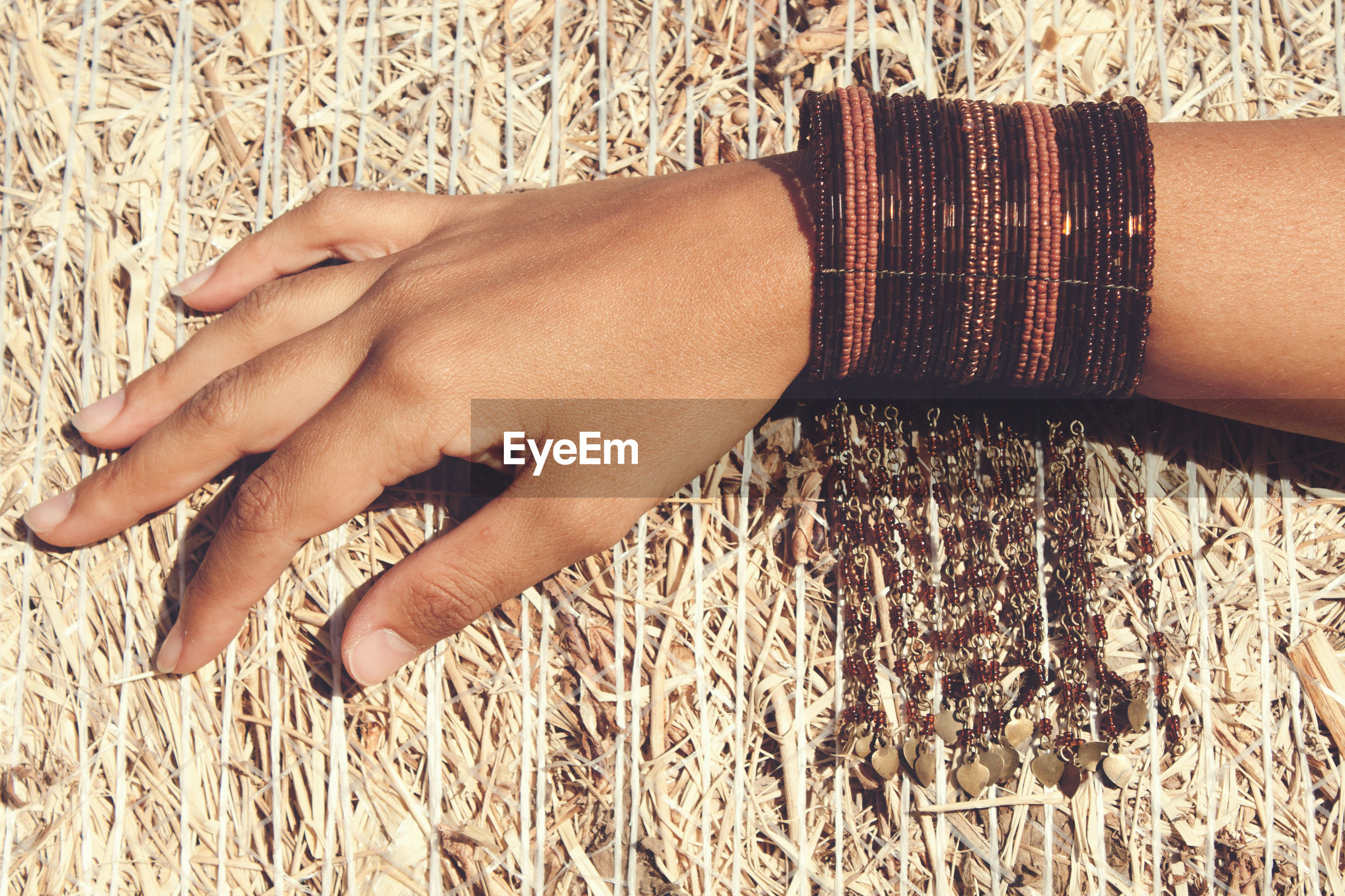 Cropped hand of woman on hay bale