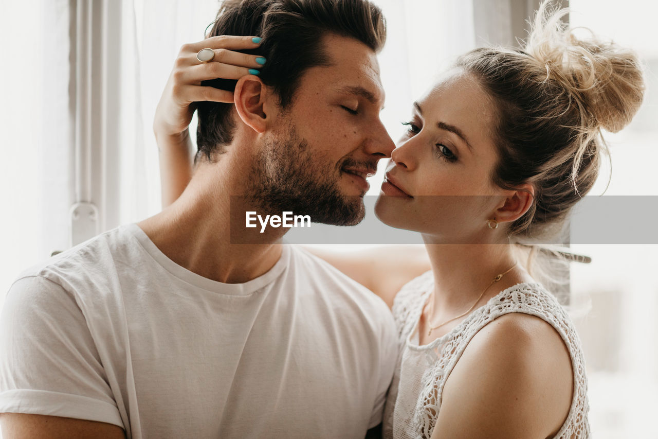 two people, young adult, togetherness, headshot, young women, love, young men, real people, portrait, indoors, lifestyles, bonding, couple - relationship, adult, focus on foreground, positive emotion, young couple, women, casual clothing, hairstyle