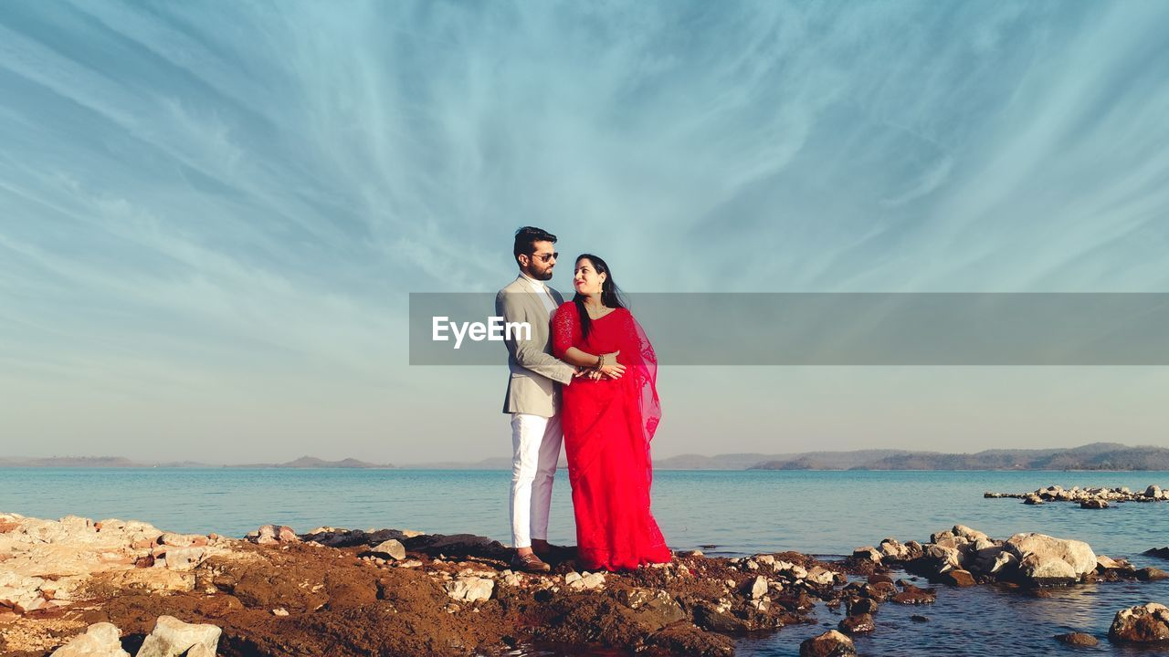 Rear view of couple standing at sea against sky
