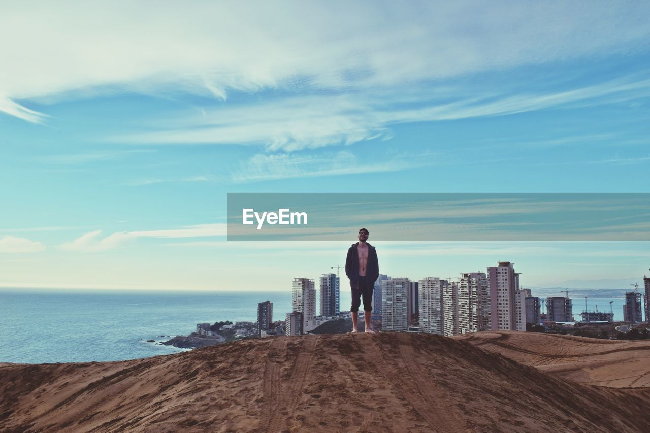 Full Length Of Man Standing On Sand Against Sea And City