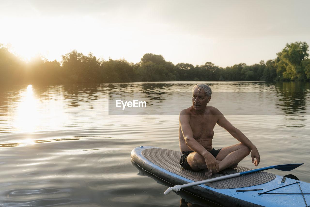 MAN SITTING ON LAKE AGAINST SKY