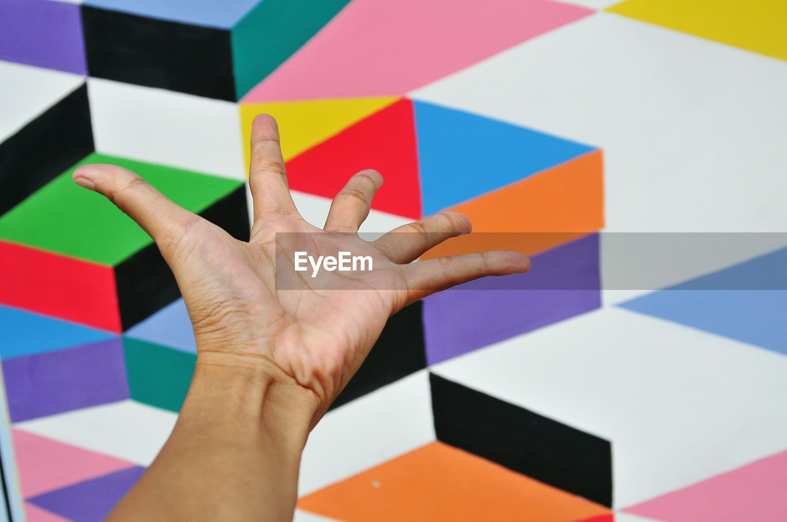 Cropped hand of person gesturing towards colorful wall