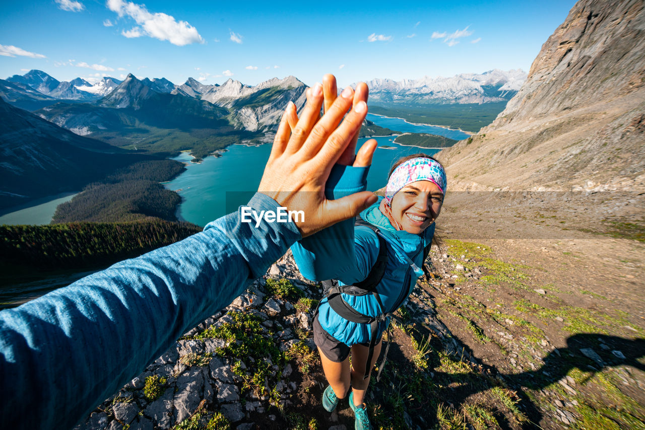 PORTRAIT OF SMILING YOUNG WOMAN WITH ARMS RAISED AGAINST MOUNTAIN