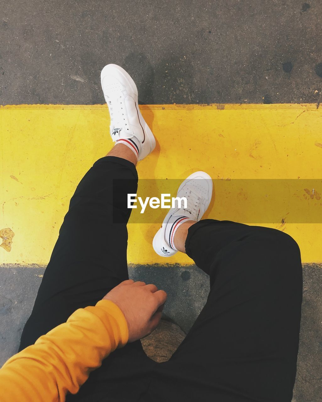 personal perspective, shoe, real people, low section, human leg, human body part, one person, yellow, body part, lifestyles, high angle view, day, men, standing, casual clothing, leisure activity, outdoors, sign, road, flooring, human foot, sock, jeans, human limb