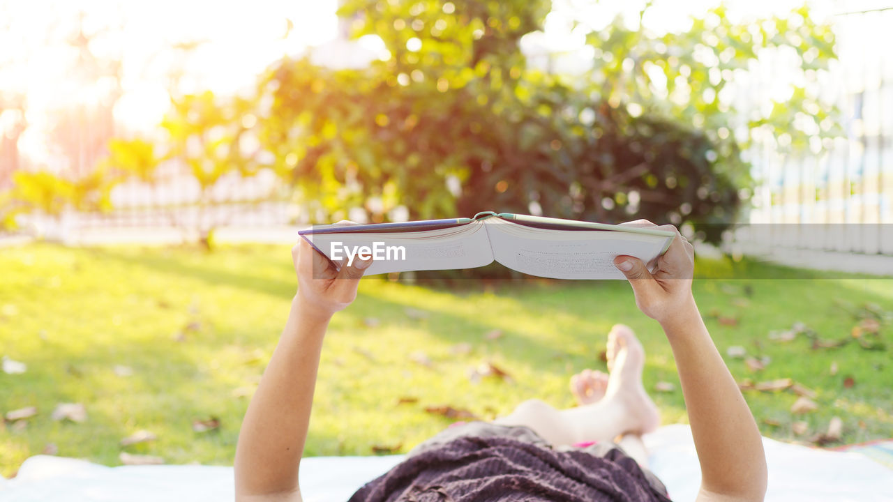 Low section of woman reading book while lying in park