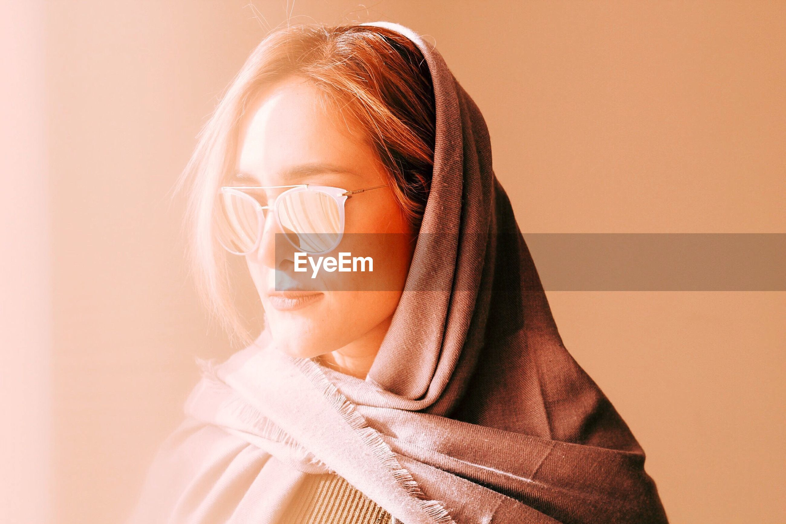 Close-up of beautiful woman in sunglasses and scarf against wall